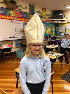 Students of St. Peter Interparish School in Jefferson City try on a home-made bishop's miter hat while learning about bishops during Catholic Schools Week.