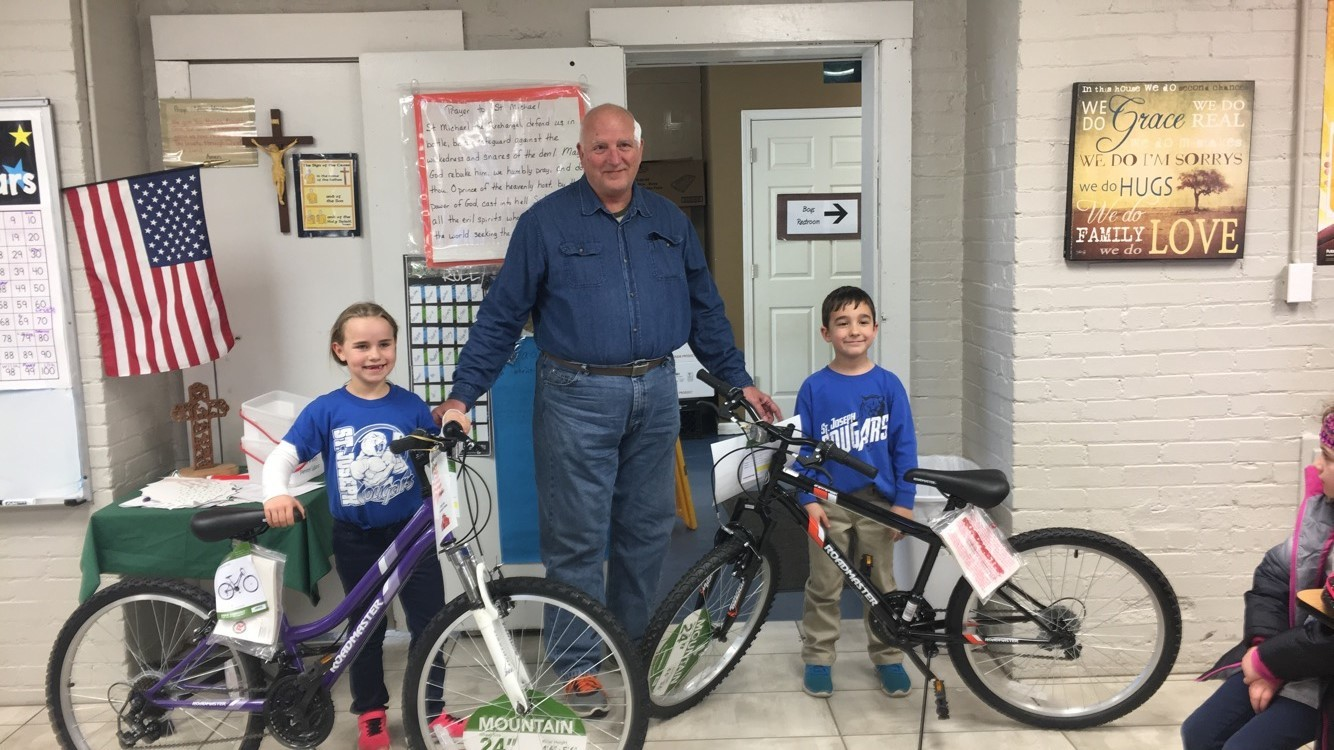 PILOT GROVE:  Audrey Wolfe and Lucas Watring are the winners of St. Joseph School's Bikes for Books contest. With them is David Booker. The contest gives students a chance to win a bicycle for reading books. Wessing Truckline and Jimmy Riley Commercial Painting donated the bikes.
