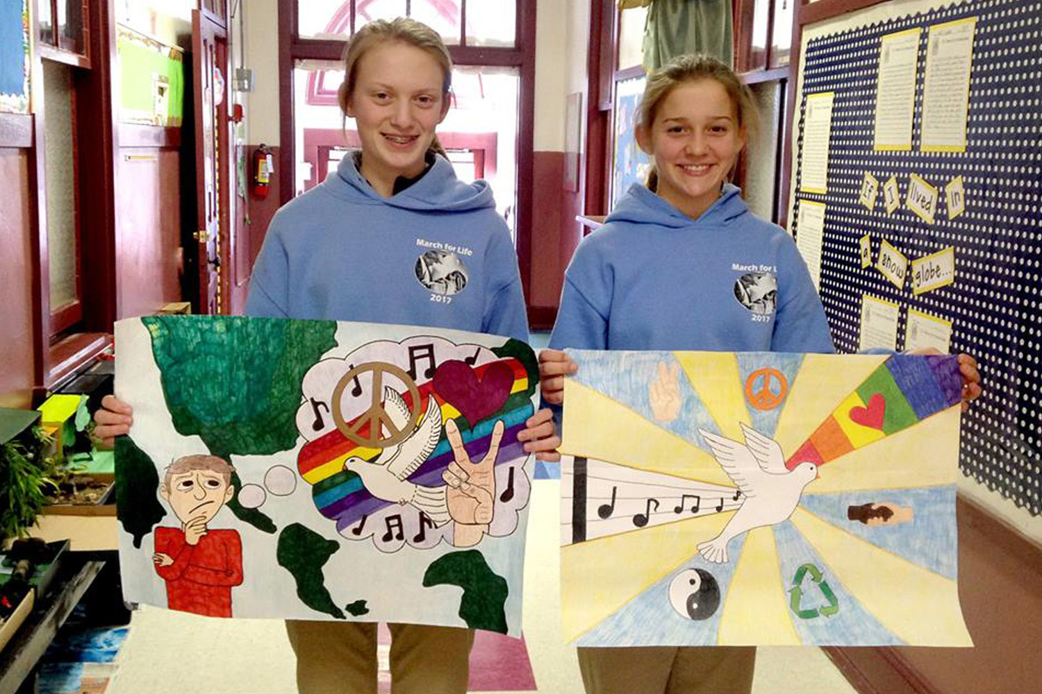 "First-place winner Malerie Schutt and second-place winner Chelsey Moeckli, both students of St. George School in Hermann, display their entries in the Hermann Lions Peace Poster contest. The theme was ""The Future of Peace."" Malerie received $50 and Chelsey received $25. Both were honored at a recent Lions Club meeting."