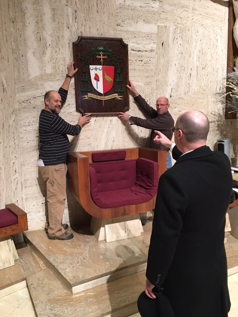 Bishop W. Shawn McKnight oversees James Hall and Ken Sargent in placing the bishop's coat of arms on the sanctuary wall above his chair in the cathedral. Mr. Hall created the wooden relief of the coat of arms. The chair, symbol of a bishop's authority over a diocese, was vacant from Nov. 21 — when Pope Francis accepted Bishop Emeritus John R. Gaydos' request for early retirement — and Bishop McKnight's ordination and installation on Feb. 6.