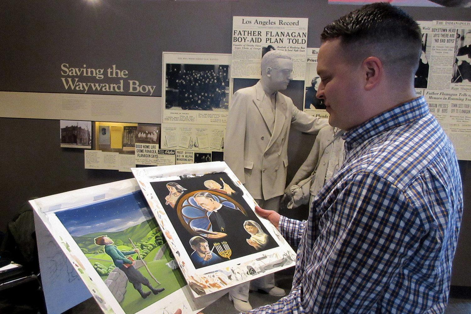 "Eli Hernandez looks over examples of his artwork for his children's book ""Dearest Children: A Message Inspired by Father Edward J. Flanagan"" March 17 at Boys Town's Hall of History museum in Omaha, Neb."