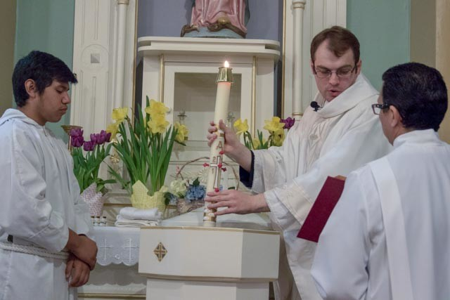 Father Dylan Schrader, who offers Mass each weekend at St. Mary parish in Milan and St. Mary parish in Unionville, blesses the holy water on Easter Sunday in the recently renovated St. Mary Church in Milan.
