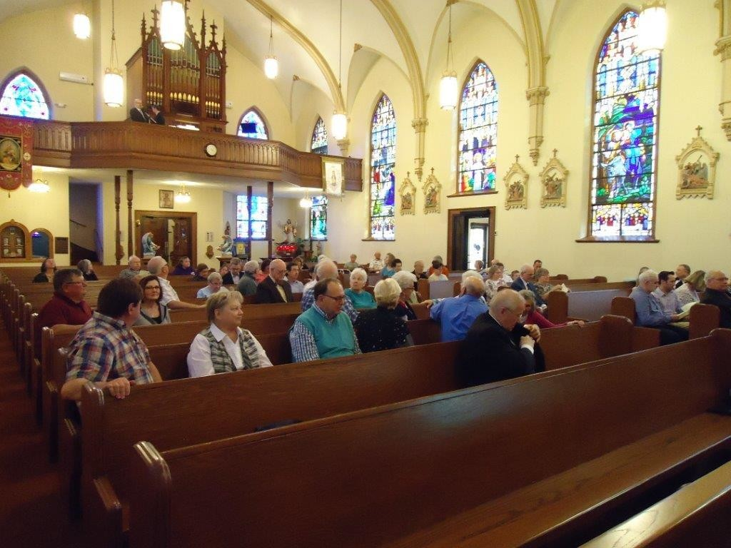 People gather inside St. Thomas the Apostle Church in St. Thomas for a concert of sacred and classic organ and trumpet music. The church's 1897 Pfeffer organ was restored in 2016.