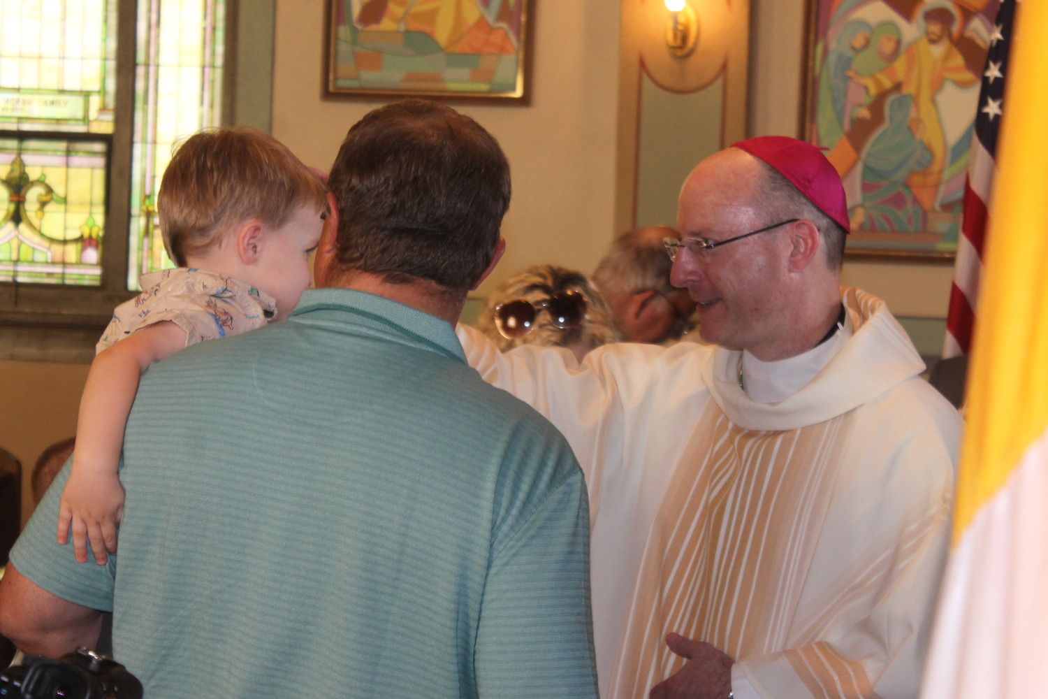 Bishop W. Shawn McKnight blesses a young parishioner during a recent visit to St. Mary parish in Milan.