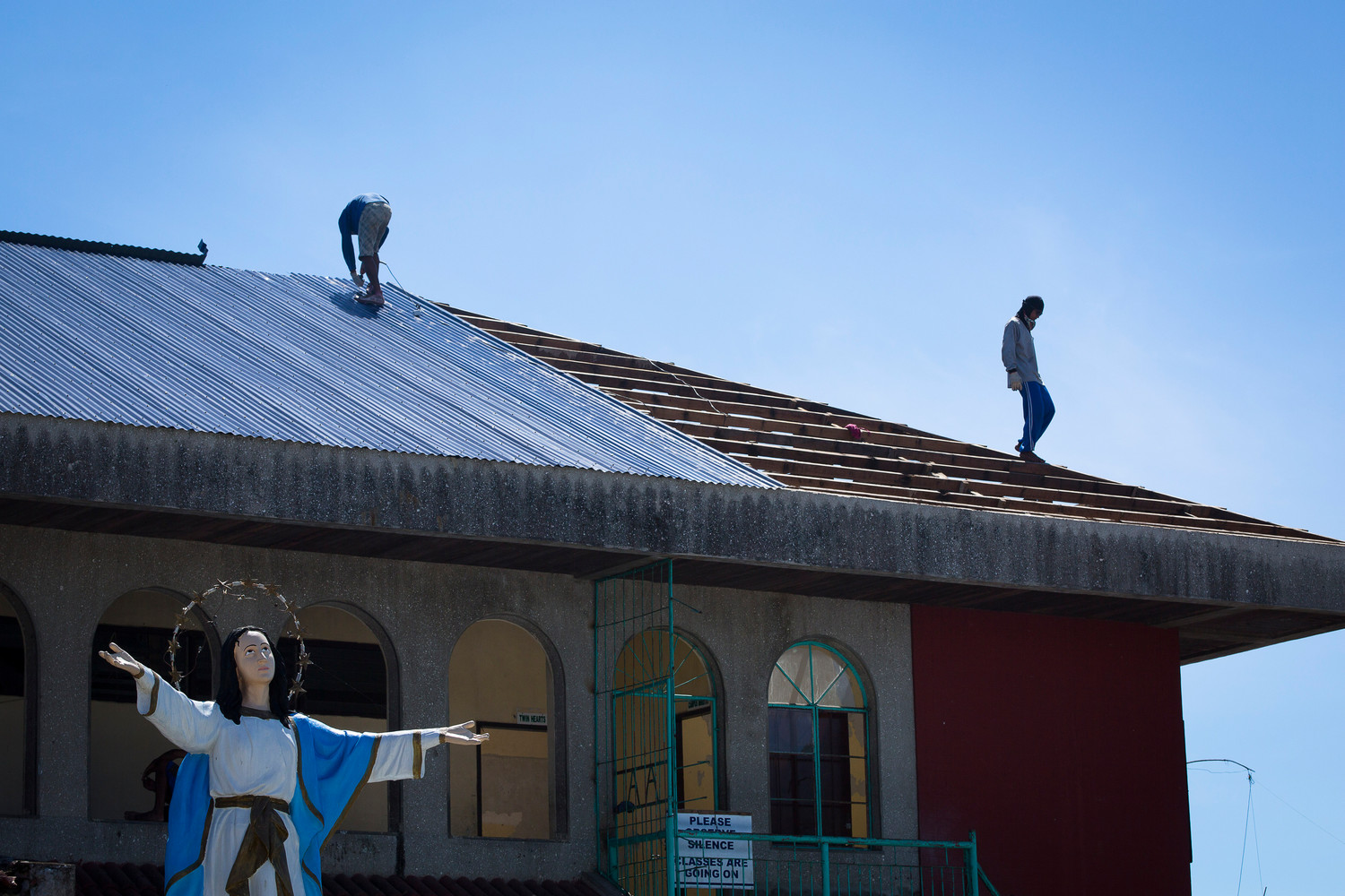 In this 2014 file photo, men replace the roof of Assumption Academy in Tanauan, Philippines, To date, the social action arm of the Catholic Church has been able to help about 1.8 million people affected by the destruction brought byr Typhoon Haiyan that struck the central Philippines in 2013.