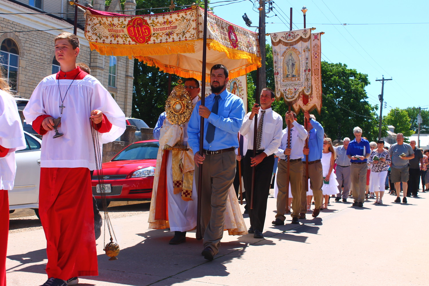 "St. Joseph parishioners follow Father Anthony Viviano, carrying the Most Blessed Sacrament, in a ""Corpus Christi"" procession down Main Street in Westphalia."