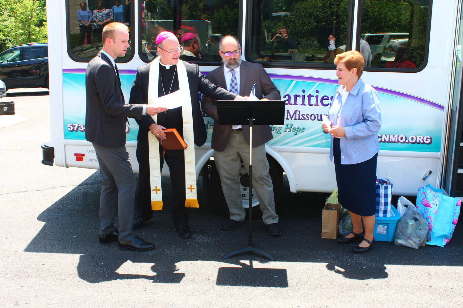 Jake Seifert, left, mission advancement director for Catholic Charities of Central and Northern Missouri (CCCNM); Executive Director Dan Lester; and Sister Kathleen Wegman SSND, chancellor of the Jefferson City diocese, join Bishop W. Shawn McKnight at a ceremony to bless CCCNM's new Mobile Resource Bus outside the Alphonse J. Schwartze Memorial Catholic Center on June 6.