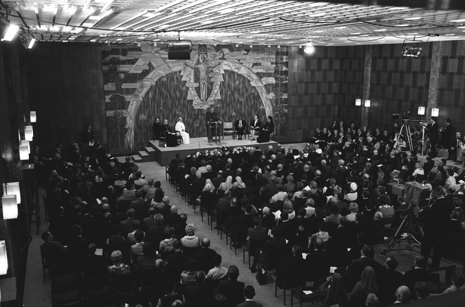 Blessed Pope Paul VI is seated as Eugene C. Blake, general secretary of the World Council of Churches, gives a speech during the Pope's visit to the WCC in Geneva, June 10, 1969. Seated to the left on the stage are: Father Pasquale Macchi, personal secretary to the Pope, and Cardinal Johannes Willebrands, president of the Pontifical Council for Promoting Christian Unity. Pope Francis is scheduled to attend an ecumenical prayer service and meeting at the WCC during a one-day visit to Geneva June 21.