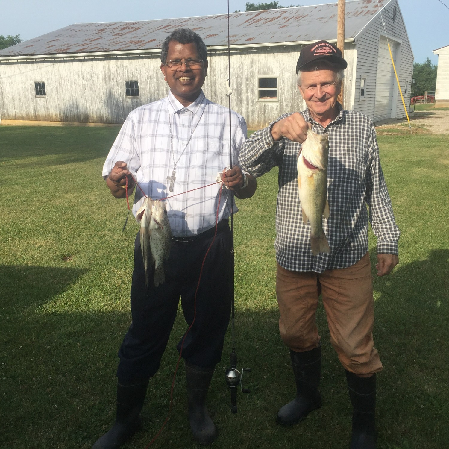 Bishop Kerketta and a member of St. Mary parish in Shelbina display fish they caught during his recent visit to the Jefferson City diocese.