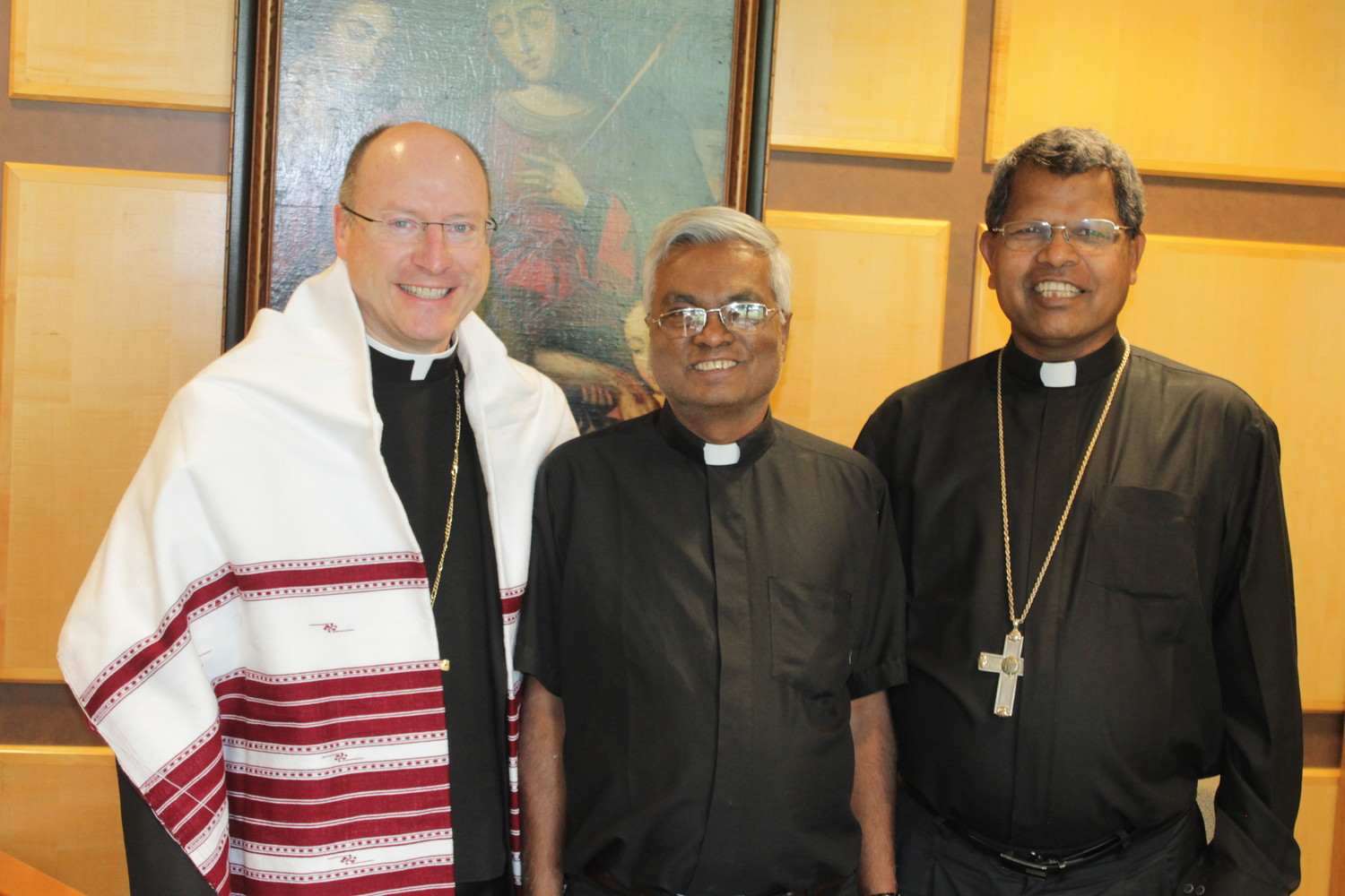 Bishop W. Shawn McKnight of Jefferson City greets Bishop Emmanuel Kerketta (right) of the Diocese of Jashpur, India during Bishop Kerketta's recent visit to the Jefferson City diocese. With them is Father Alex Ekka, a priest of the Jashpur diocese who is serving in Warsaw and Cole Camp. Bishop Kerketta presented Bishop McKnight a hand-woven turban, a symbol of royalty and great honor.
