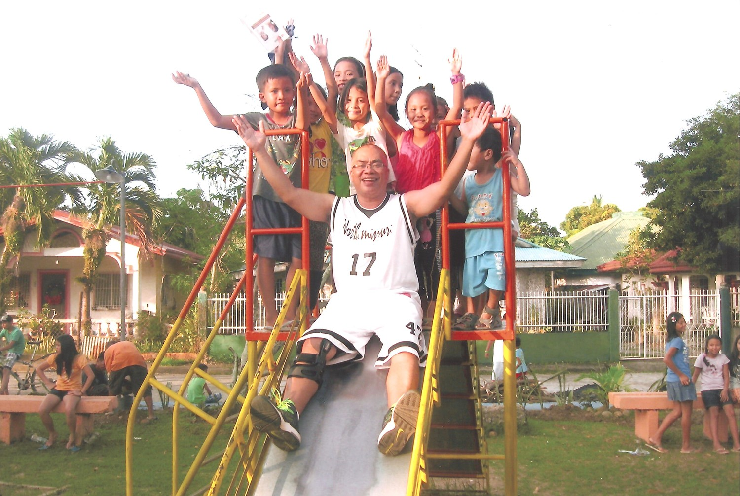"Father Donardo ""Dandi"" Bermejo, who served for almost a decade in the Jefferson City diocese, joins children of sugar plantation workers in trying-out a new playground he helped to get built in one of the communities he ministers to on his home island of Negros Occidental in the Philippines."