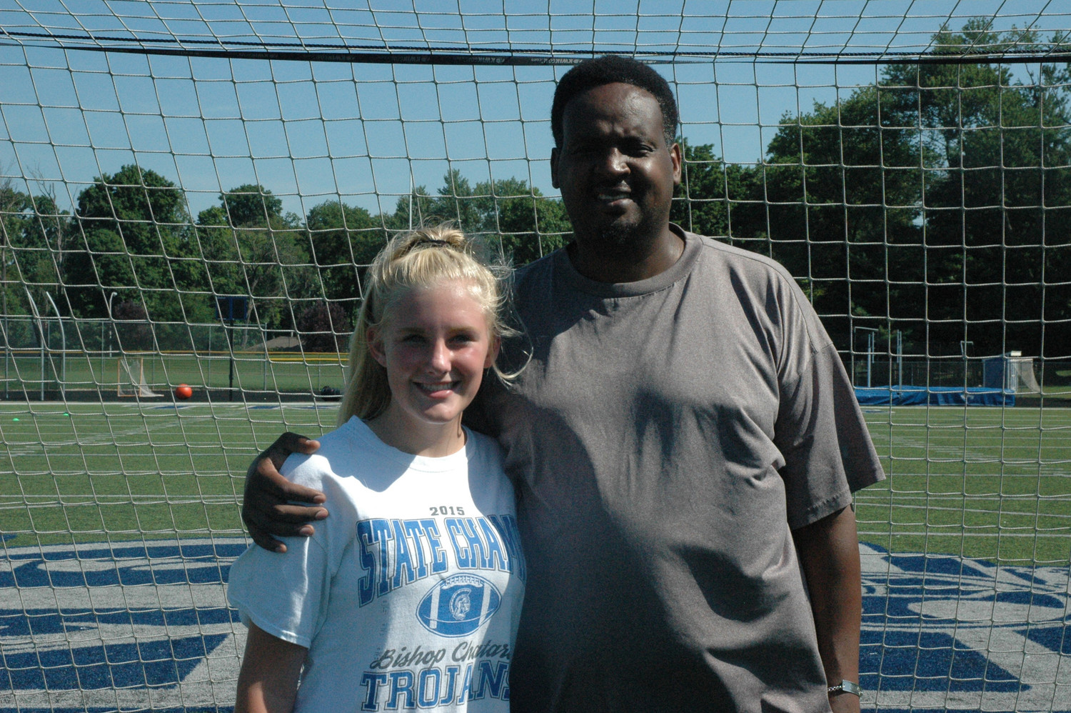 Kizito Kalima, right, a survivor of the 1994 genocide in Rwanda, poses for a photo with 16-year-old Olivia Julian June 29 at Bishop Chatard High School in Indianapolis, where he held a soccer clinic for youths born in the refugee camps of that African country.