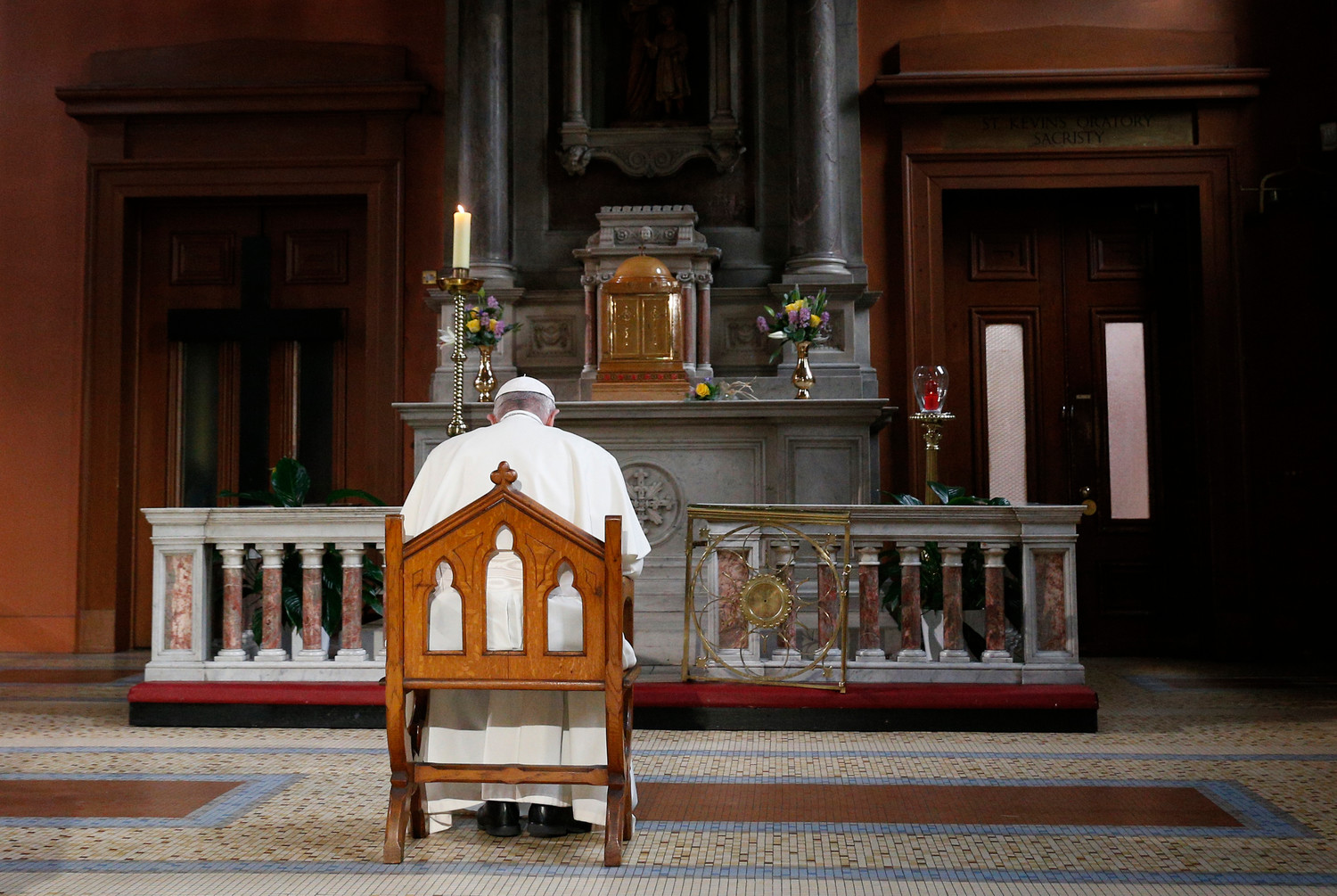 Pope Francis prays in front of a candle in memory of victims of sexual abuse as he visits St. Mary's Pro-Cathedral in Dublin Aug. 25.