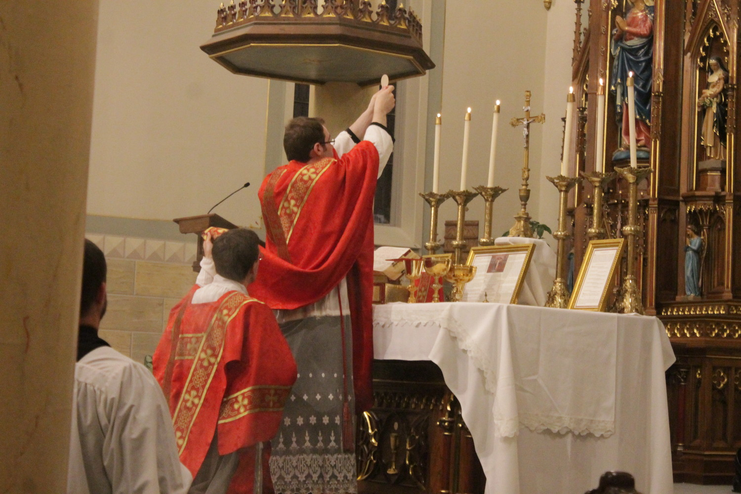 Father Dylan Schrader elevates the Most Blessed Sacrament while offering Mass in the extraordinary form in Latin on Sept. 14, the Feast of the Exultation of the Cross, in St. Peter Church in Jefferson City.