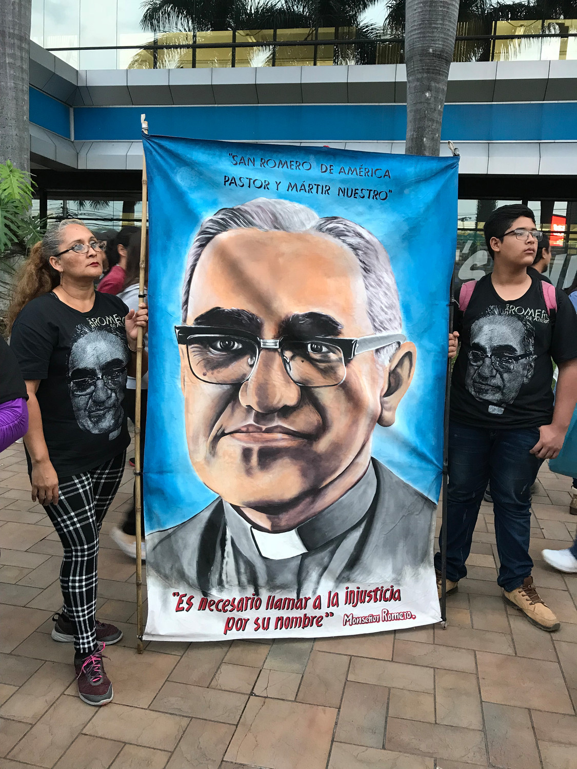 A woman and young man hold a banner of St. Oscar Romero Oct. 13 in San Salvador, El Salvador. Pope Francis celebrated the canonization Mass for St. Oscar Romero and six other new saints in St. Peter's Square Oct. 14 at the Vatican.
