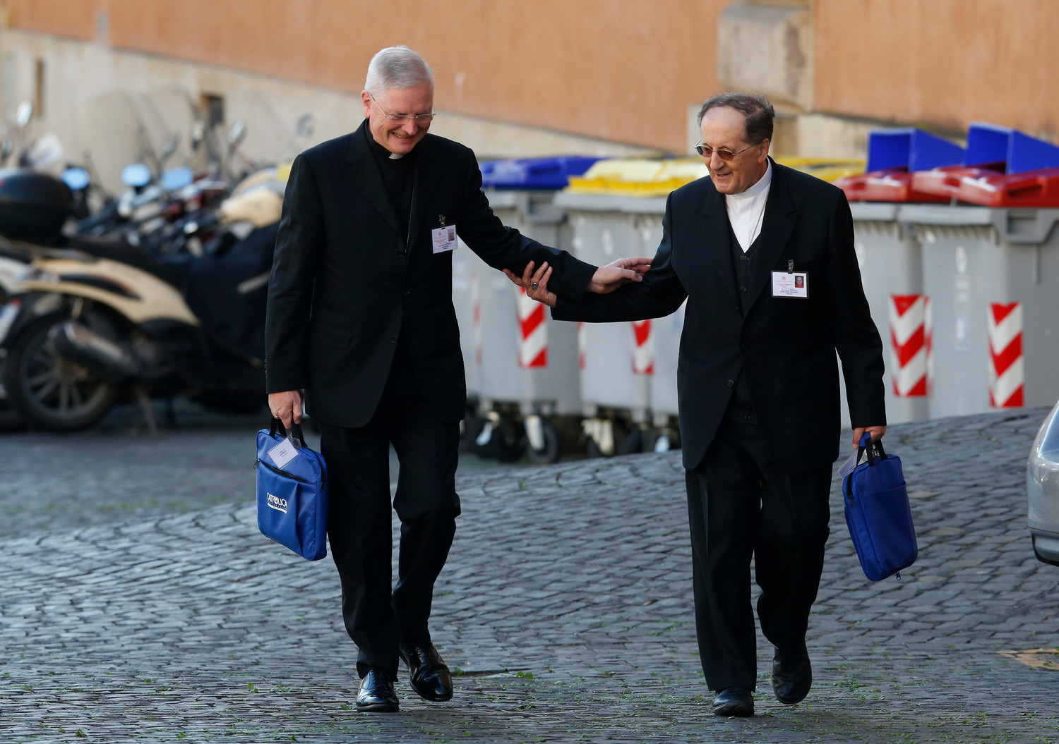 "Archbishop Leo Cushley of St. Andrews and Edinburgh, Scotland, and Cardinal Beniamino Stella, prefect of the Congregation for Clergy, exchange greetings as they walk to a session of the Synod of Bishops on young people, the faith and vocational discernment at the Vatican Oct. 8. In his speech at the synod, Cardinal Stella warned of the phenomenon of ""wandering seminarians"" who move from one diocese to another."
