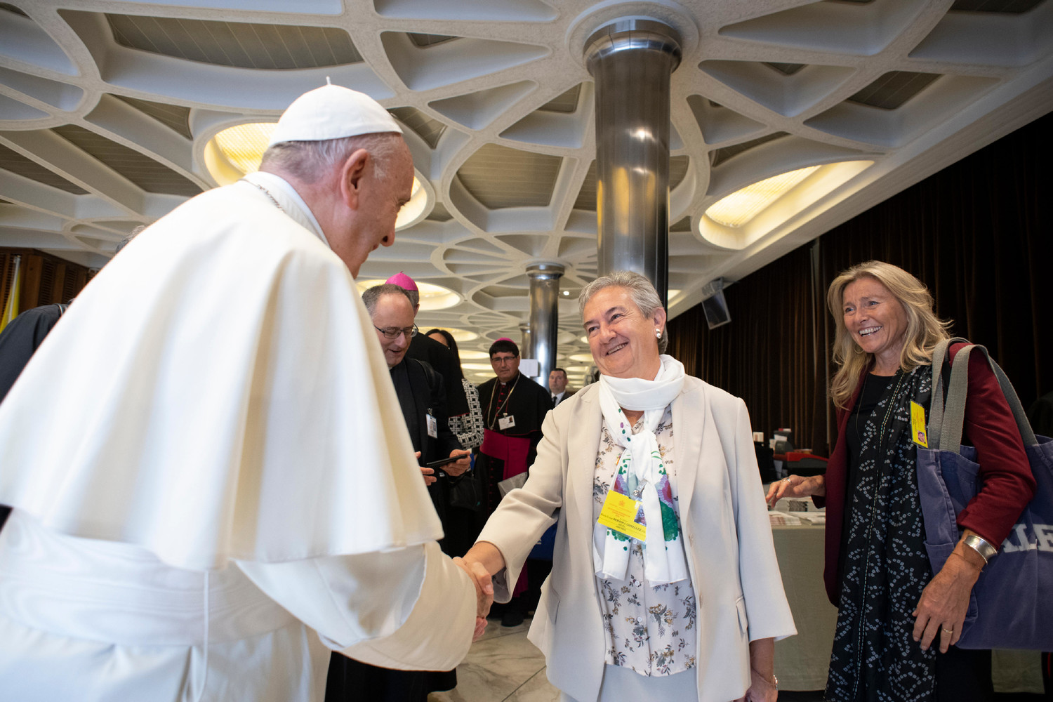 Pope Francis greets Sister Maria Luisa Berzosa Gonzalez before a session of the Synod of Bishops on young people, the faith and vocational discernment at the Vatican Oct. 16. Also pictured is Chiara Giaccardi, an Italian professor of sociology.