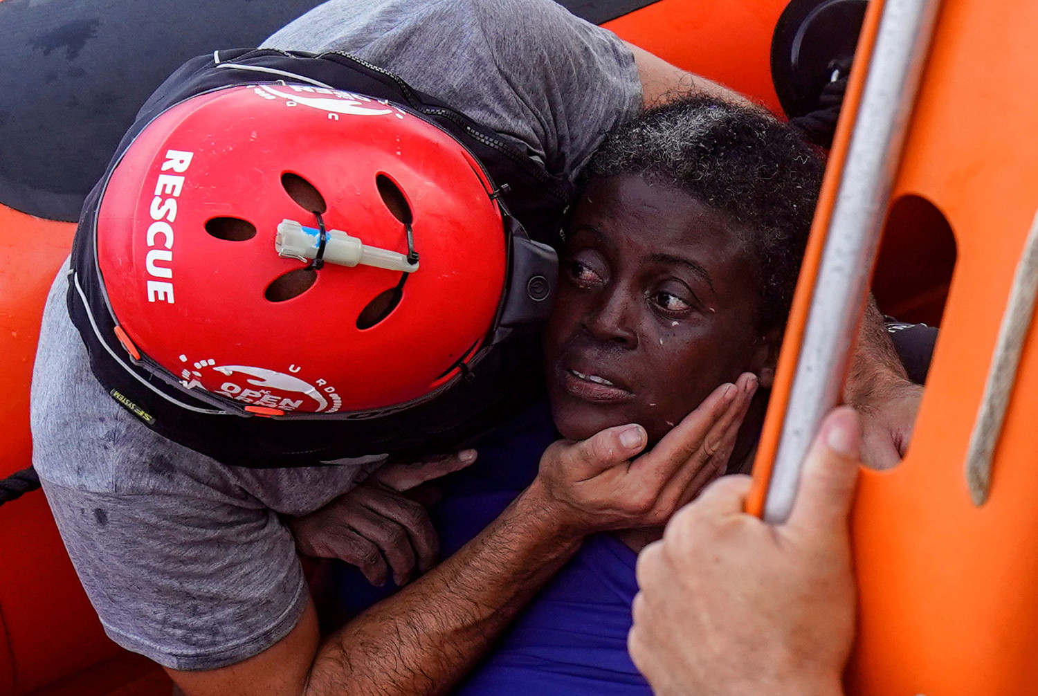 A crew member of the Spanish nongovernmental organization Proactiva Open Arms comforts a rescued African migrant July 17 in central Mediterranean Sea. The main mission of the NGO is sea rescues of refugees that arrive in Europe fleeing wars, persecution or poverty.