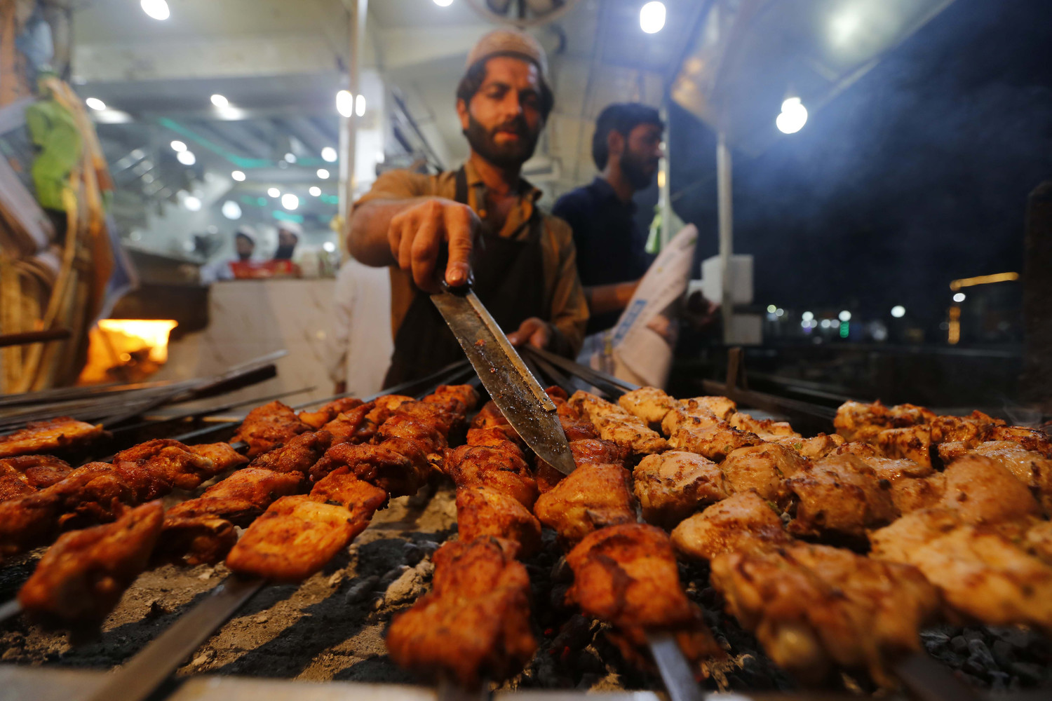 A man sells roasted chicken on a road in Peshawar, Pakistan Oct. 15, the eve of World Food Day. The international day is celebrated Oct. 16 to mark the date in 1945 the U.N. Food and Agriculture Organization was founded.