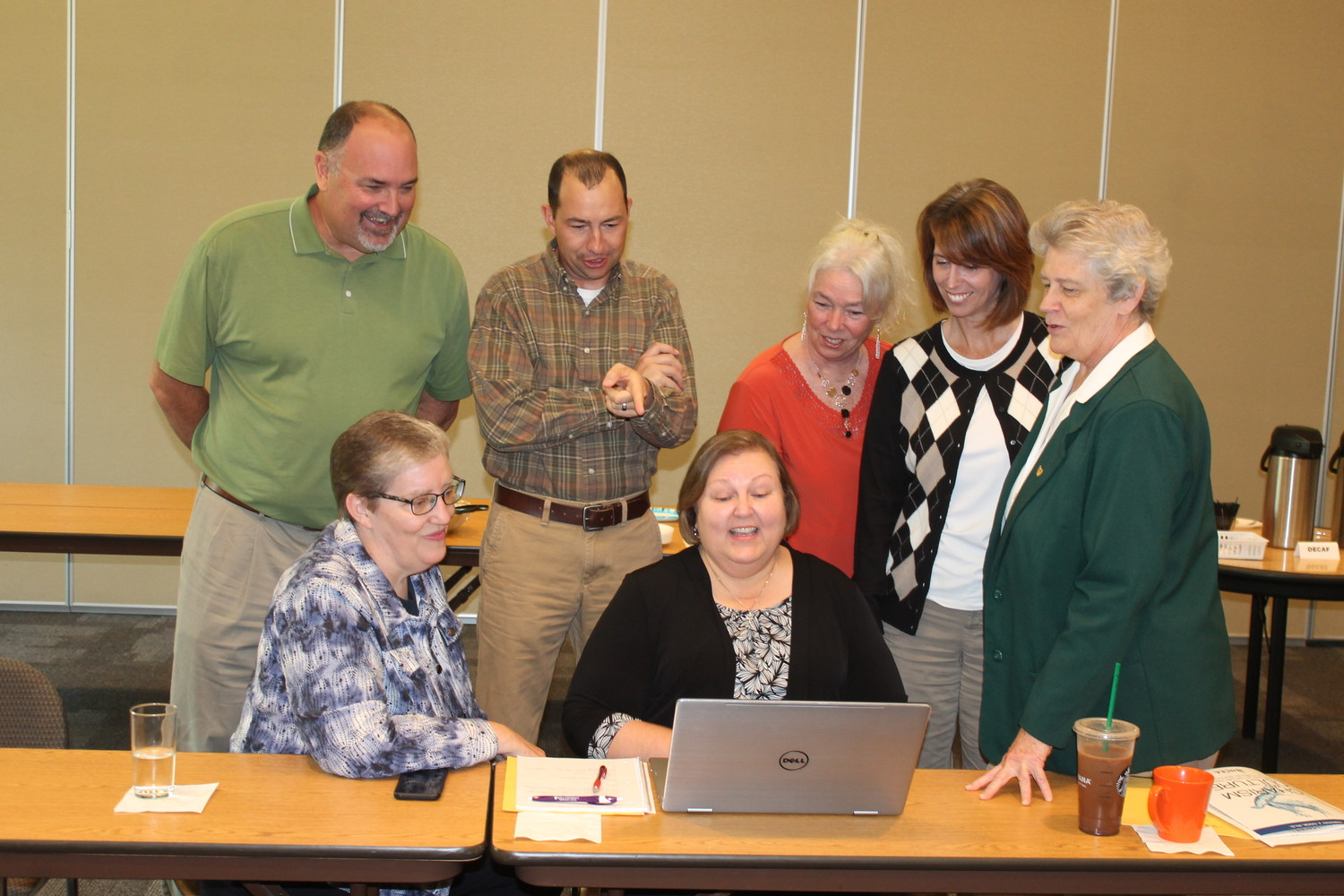 Sister Julie Brandt SSND, diocesan associate superintendent of Catholic schools, seated at left, and Sister Elizabeth Youngs SCL, diocesan school superintendent, standing at right, visit with Catholic school principals during a meeting in Jefferson City Oct. 30.