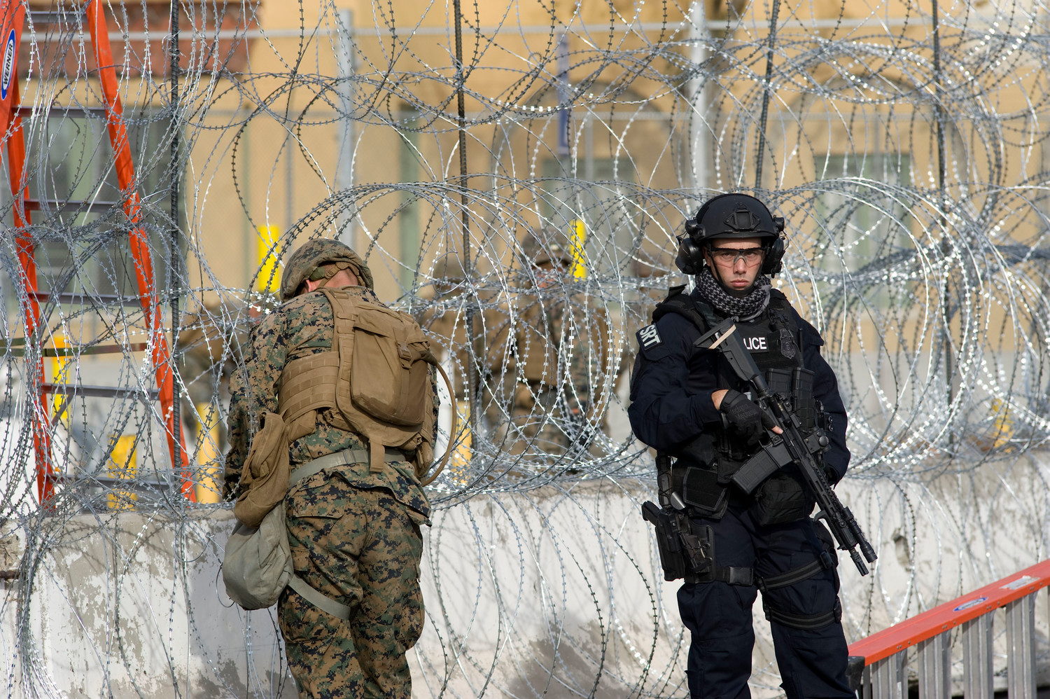 A U.S. Customs and Border Protection officer, right, stands next to a member of the U.S. military working with concertina wire during a show of force and exercise to secure the San Ysidro Port of Entry Nov. 22 in San Diego. Several hundred officers as well as military personnel were seen participating in the exercise, which had the border crossing closed for about 30 minutes. The show of force and exercise was in response to the presence of a large caravan of mainly Honduran migrants that recently arrived in neighboring Tijuana, Mexico.