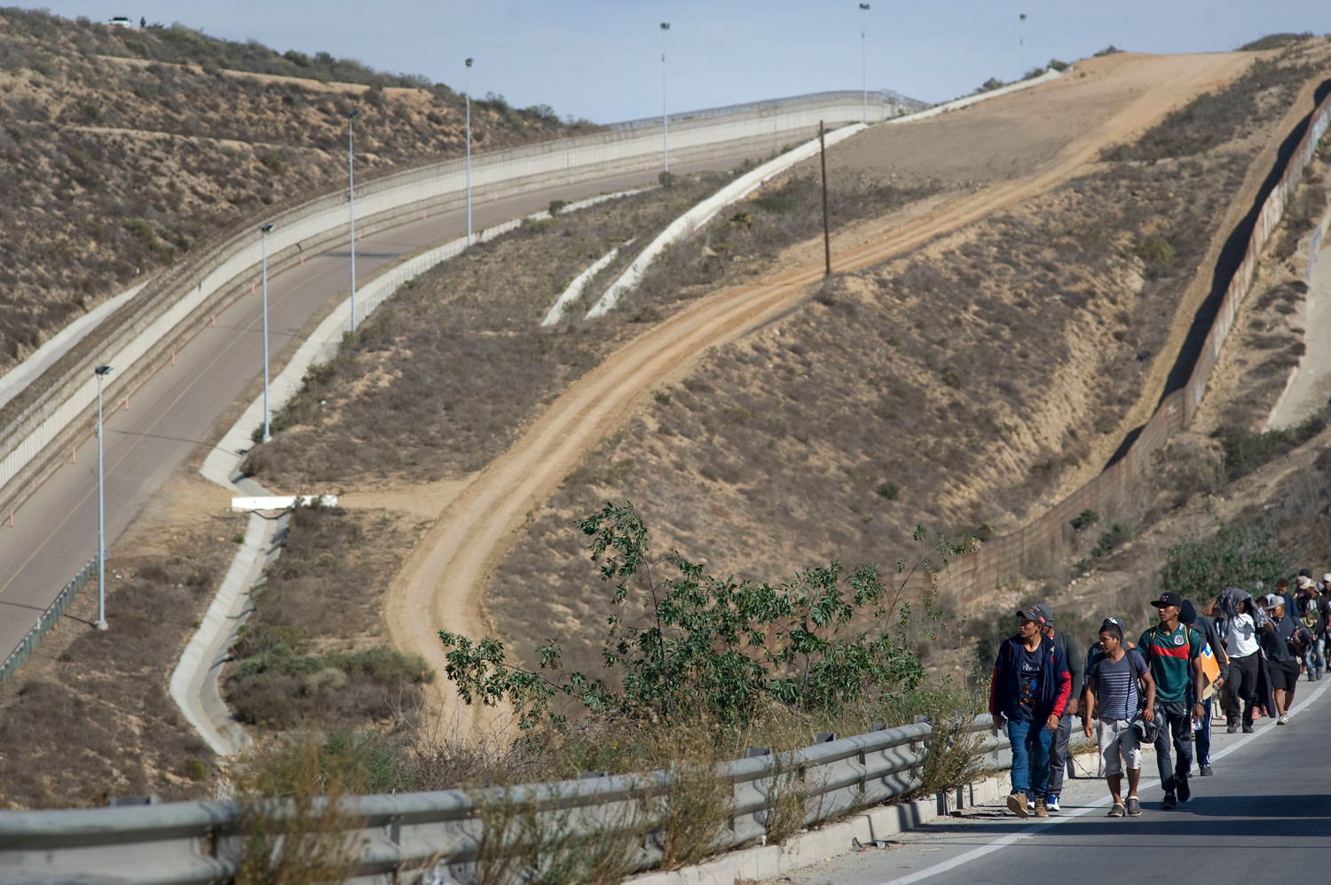 A group of about 350 Central American migrants walk along the highway toward the beach Nov. 13 after arriving in Tijuana, Mexico. The group split from and advanced ahead of a larger caravan making its way to the border.