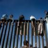 Part of a group of about 350 Central American migrants sit on the U.S.-Mexico border fence Nov. 13 in Tijuana, Mexico. The group split from and advanced ahead of a larger caravan making its way to the border.