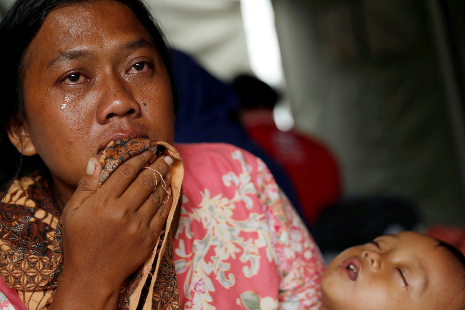 An Indonesian woman cries as she holds a child Dec. 25 at an evacuation center in Labuhan after a tsunami hit two islands. Indonesian authorities asked people to avoid the coast in areas where the tsunami killed more than 400 people.