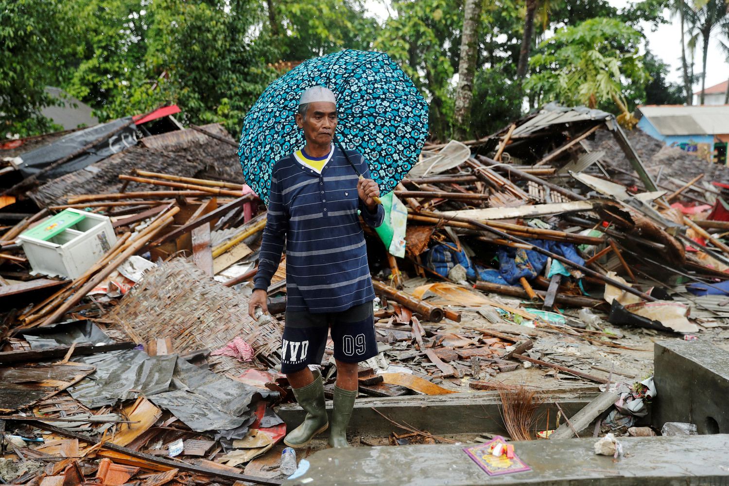 An Indonesian man walks through the debris of his destroyed house in Sumur Dec. 26 after a tsunami hit two islands. Indonesian authorities asked people to avoid the coast in areas where the tsunami killed more than 400 people.
