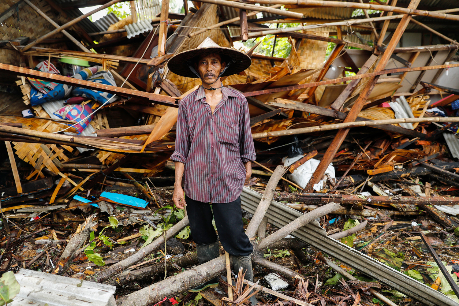An Indonesian man stands in front of his destroyed house Dec. 24 after a tsunami hit two islands. Indonesian authorities asked people to avoid the coast in areas where the tsunami killed more than 400 people.