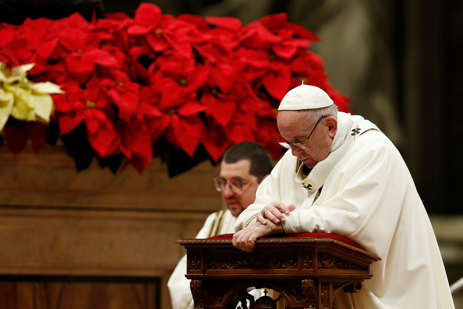 Pope Francis kneels in prayer as he celebrates Christmas Eve Mass in St. Peter's Basilica at the Vatican Dec. 24.