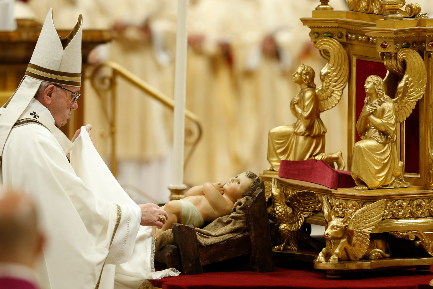 Pope Francis unveils a figurine of the baby Jesus at the start of Christmas Eve Mass in St. Peter's Basilica at the Vatican Dec. 24.