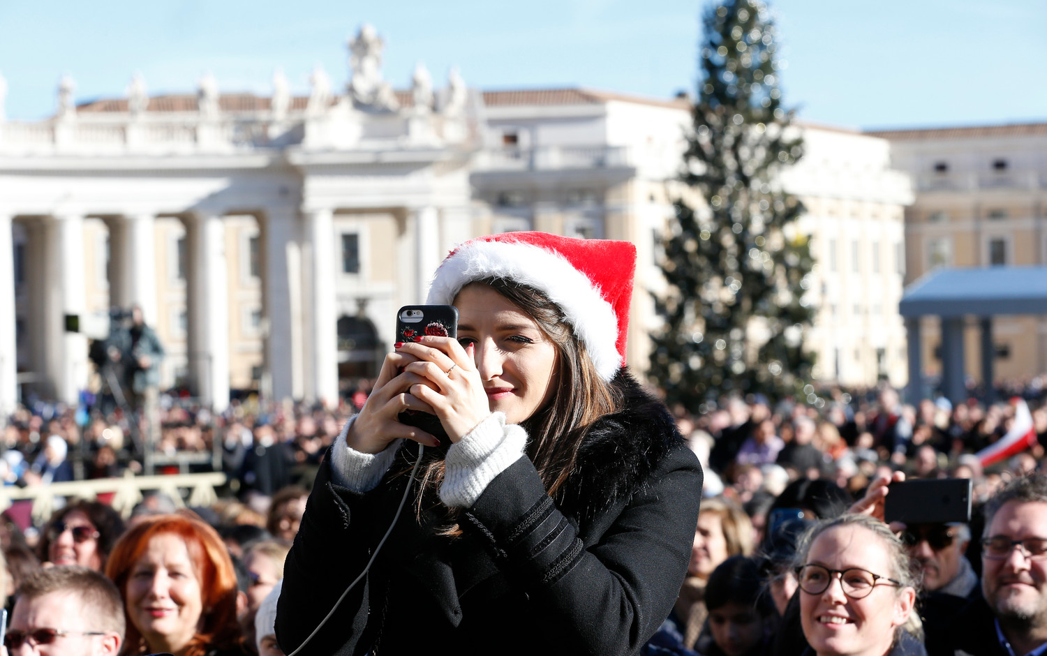 "A woman takes a photo before Pope Francis' Christmas message and blessing ""urbi et orbi"" (to the city and the world) delivered from the central balcony of St. Peter's Basilica at the Vatican Dec. 25."