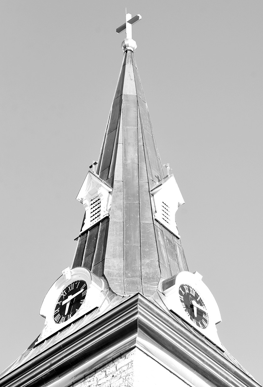 A close-up photo shows the recently completed coppor cornice, steeple roof, repainted dormers and clocks and refurbished stainless-steel cross atop the 1848-vintage St. Joseph Church in Westphalia.