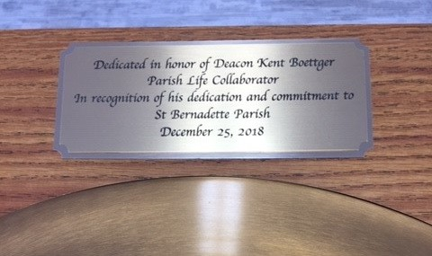 This plaque adorns the recently dedicated baptismal font in St. Bernadette Church in Hermitage.