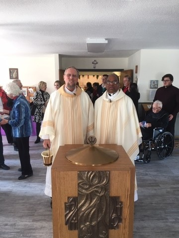 Deacon Kent Boettger, parish life collaborator at St. Bernadette, and Father Angelus Minj, sacramental minister, stand by the font after Mass on Christmas Day.