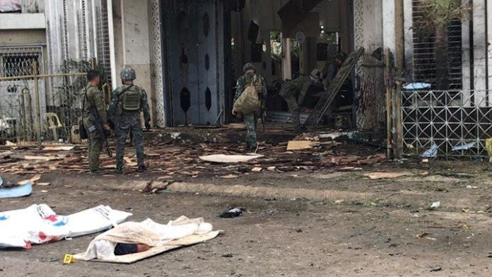 Philippine army soldiers walk near covered bodies as they inspect damage outside the Cathedral of Our Lady of Mount Carmel following a bomb blast in Jolo Jan. 27, 2019. The explosion, just before morning Mass, killed at least 20 people and wounded dozens of others.