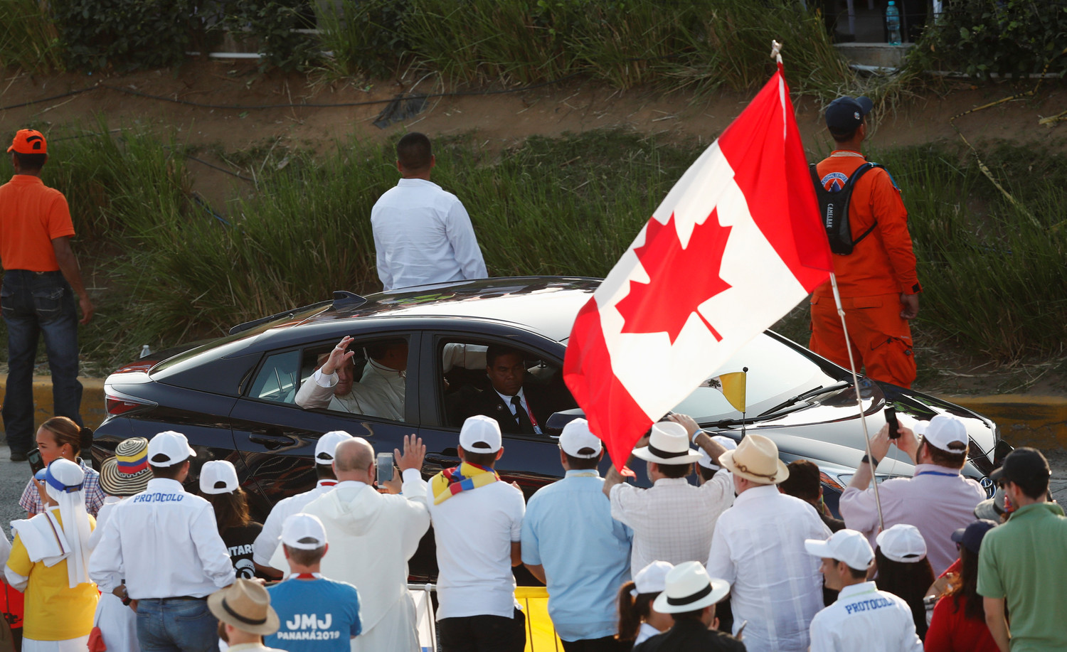 Pope Francis waves to World Youth Day pilgrims near a Canadian flag as he arrives to lead the Way of the Cross at Santa Maria la Antigua Field in Panama City Jan. 25, 2019.