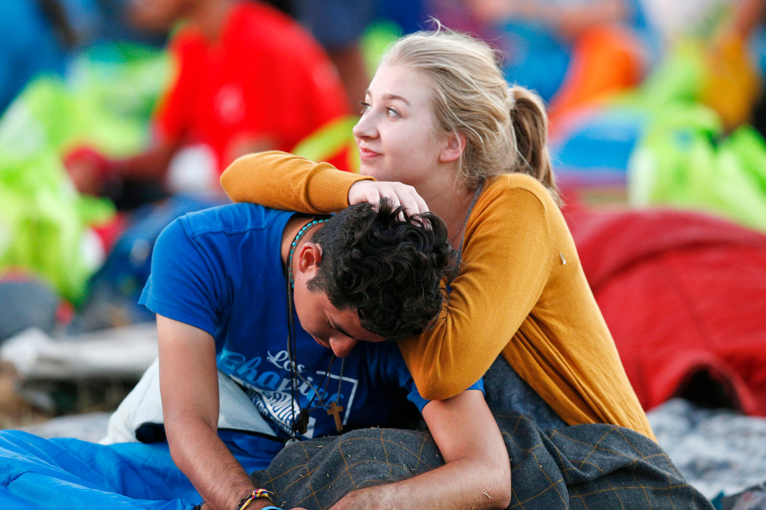 A young couple wake up before Pope Francis' celebration of Mass for World Youth Day pilgrims at St. John Paul II Field in Panama City Jan. 27, 2019.