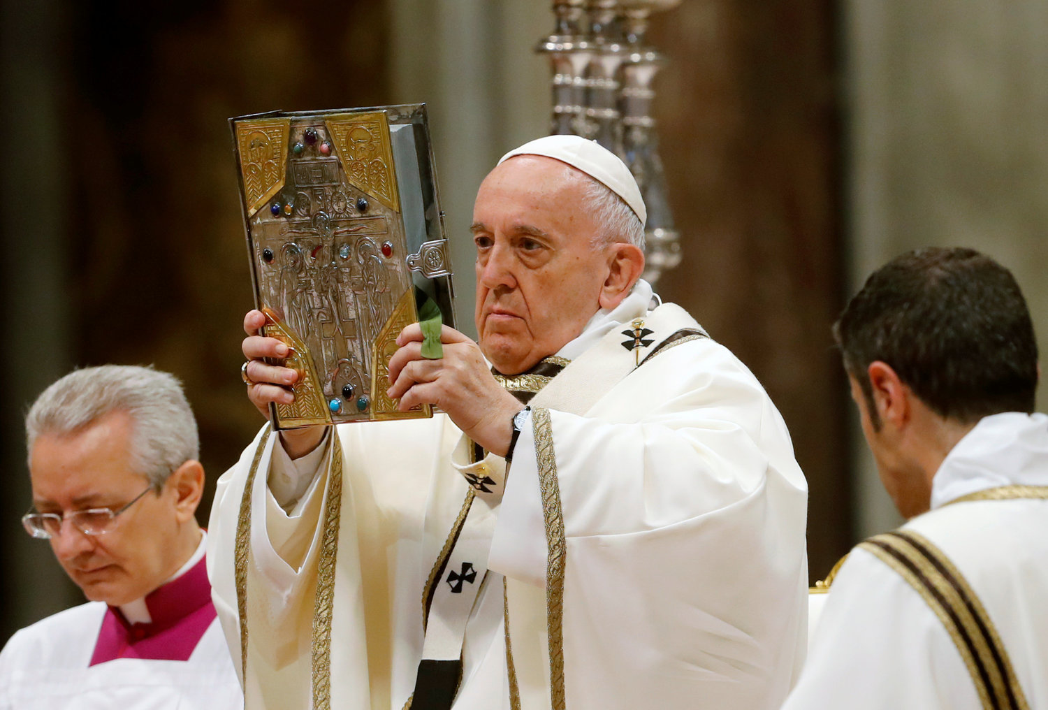 Pope Francis raise the Book of the Gospels as he celebrates Mass on Holy Thursday in St. Peter's Basilica at the Vatican April 18, 2019.