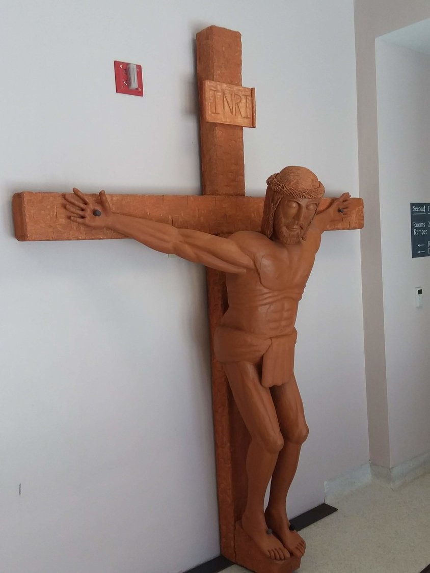 This carved wooden crucifix that adorns the student entrance to the St. Thomas More Newman Center in Columbia was made by Deacon Fred Weisel.