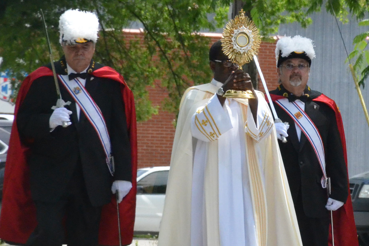 Father Augustine Okoli, administrator of the parishes in Martinsburg, Montgomery City, Jonesburg and Wellsville, carries the Most Blessed Sacrament in procession on the Solemnity of the Body and Blood of Christ in 2017.