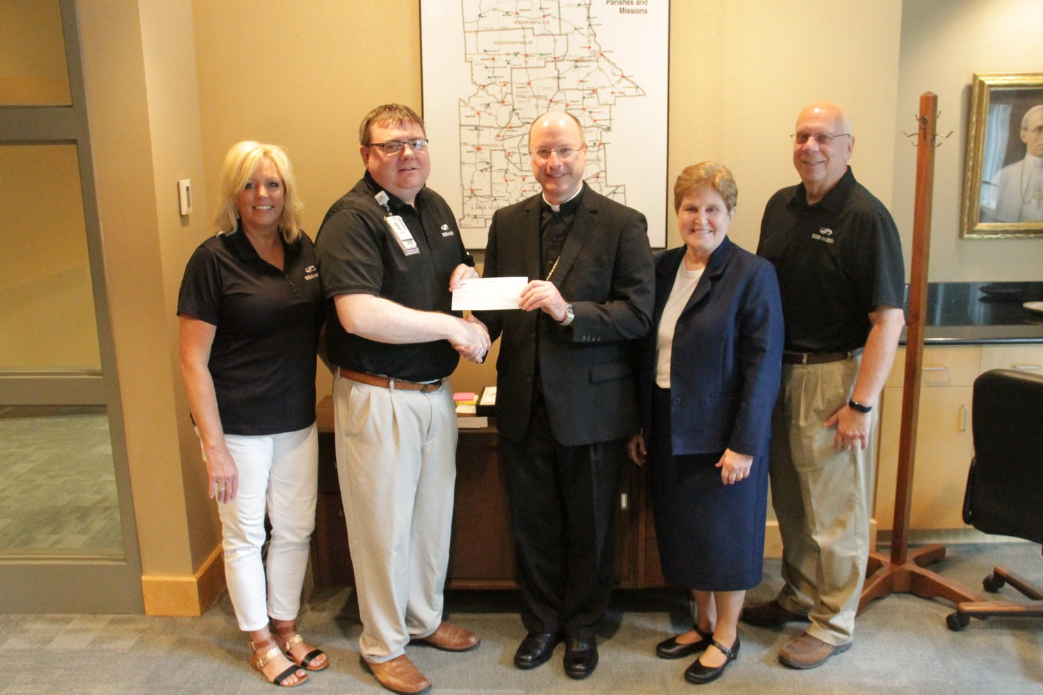 Joshua L. Allee, regional mission leader for SSM Health Mid-Missouri, presents to Bishop W. Shawn McKnight of the Jefferson City diocese a check for $25,000 for Catholic Charities of Central and Northern Missouri's Disaster Relief Fund. With them, from left, are Mike Baumgartner, president of SSM Health Mid-Missouri; Sister Kathleen Wegman of the School Sisters of Notre Dame, the diocese's director of pastoral and charitable services and liaison for Catholic healthcare; and Bev Stafford, director of the St. Mary's Foundation.