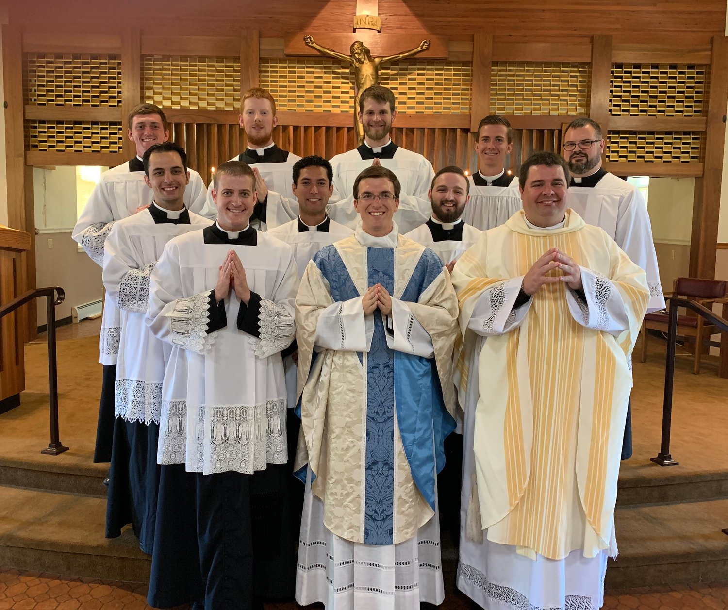 Newly ordained Father Brad Berhorst (center) joins Father Joshua Duncan, Father Christopher Aubuchon and semi-narians of the Jefferson City diocsese in the sanctuary of St. Martin Church in St. Martins following Fr. Berhorst's Mass of Thanksgiving there on June 30.
