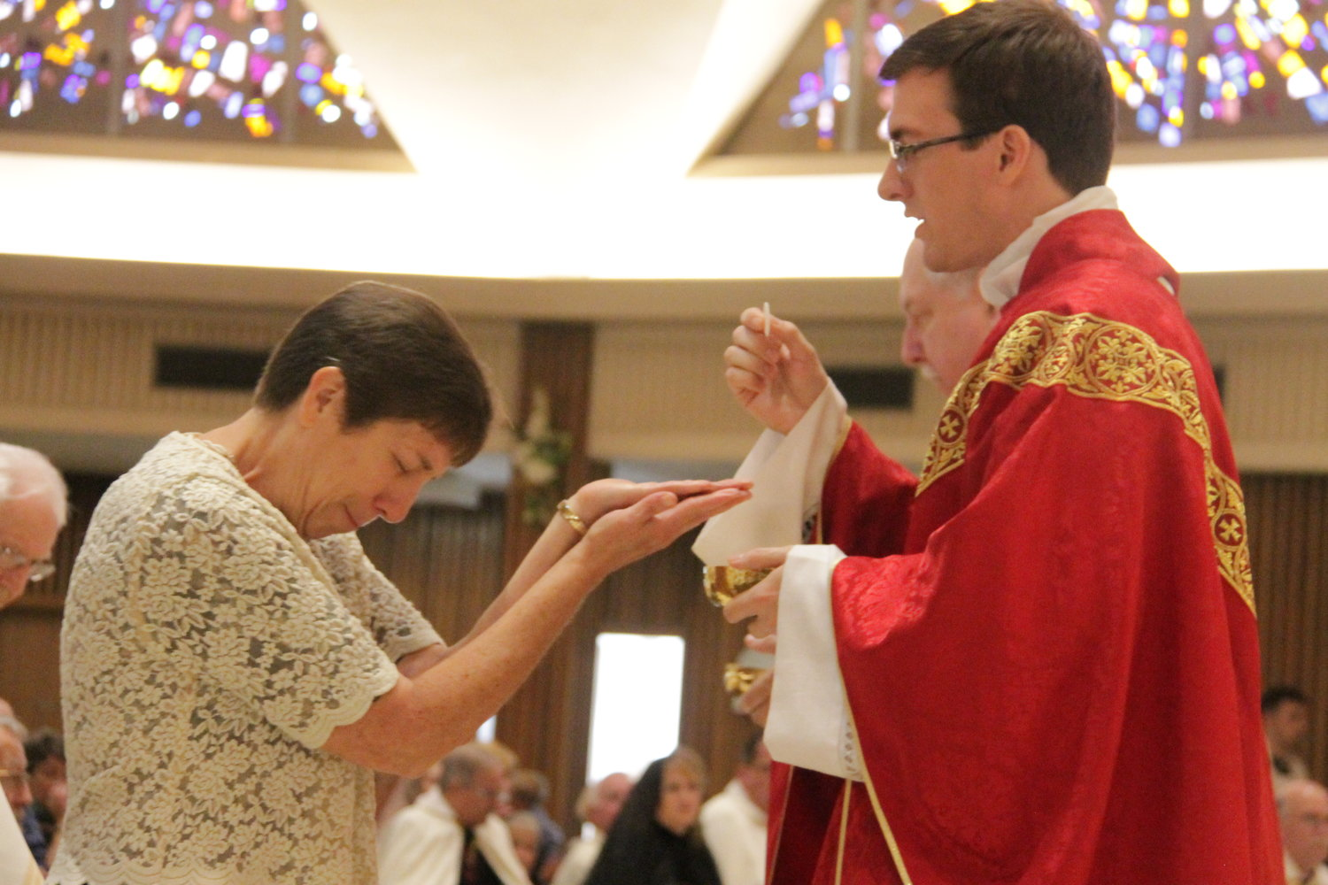 Newly ordained Father Brad Berhorst gives Holy Communion to his mother, Rosemary Berhorst, during his Ordination Mass.