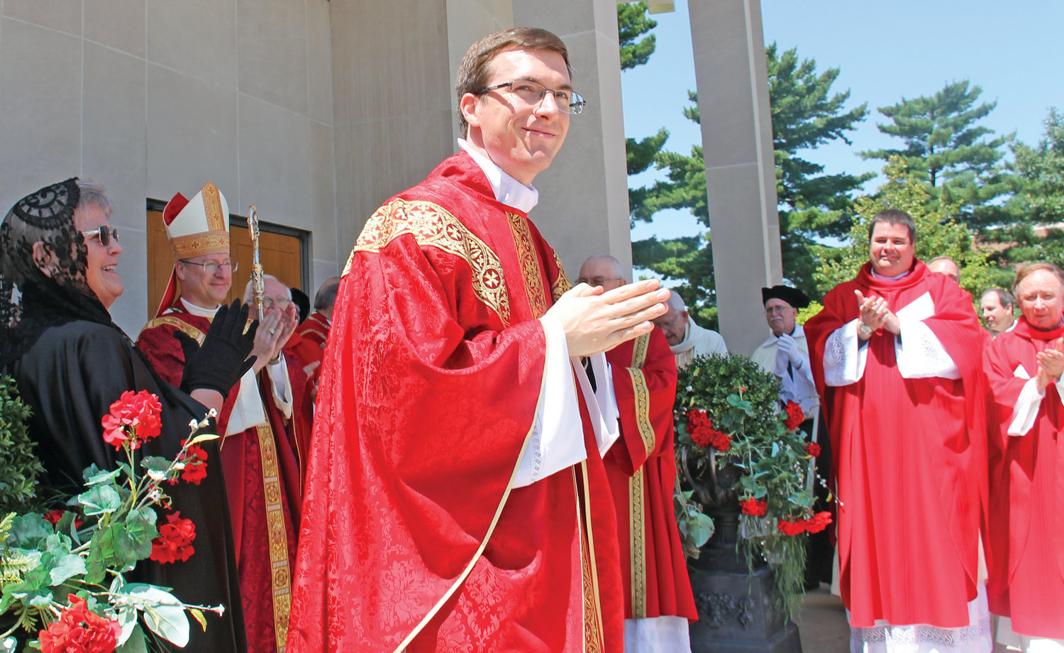 As his brother priests applaud, Father Brad Berhorst steps out of the Cathedral of St. Joseph in Jefferson City following his ordination to the Priesthood on June 29.