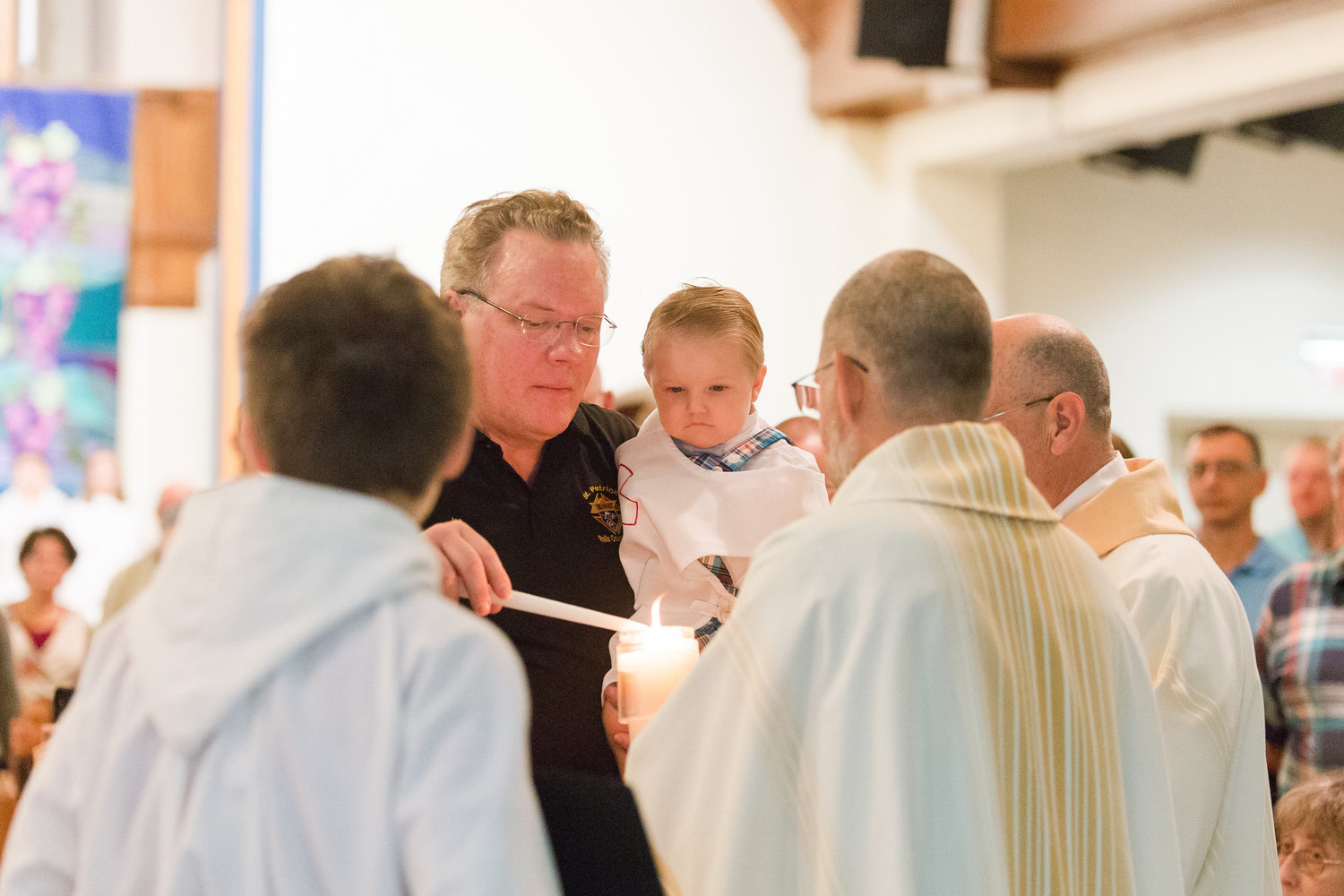 Joe Dalton, Noah's godfather, lights his baptismal candle from the Easter candle at St. Patrick Church in Rolla.