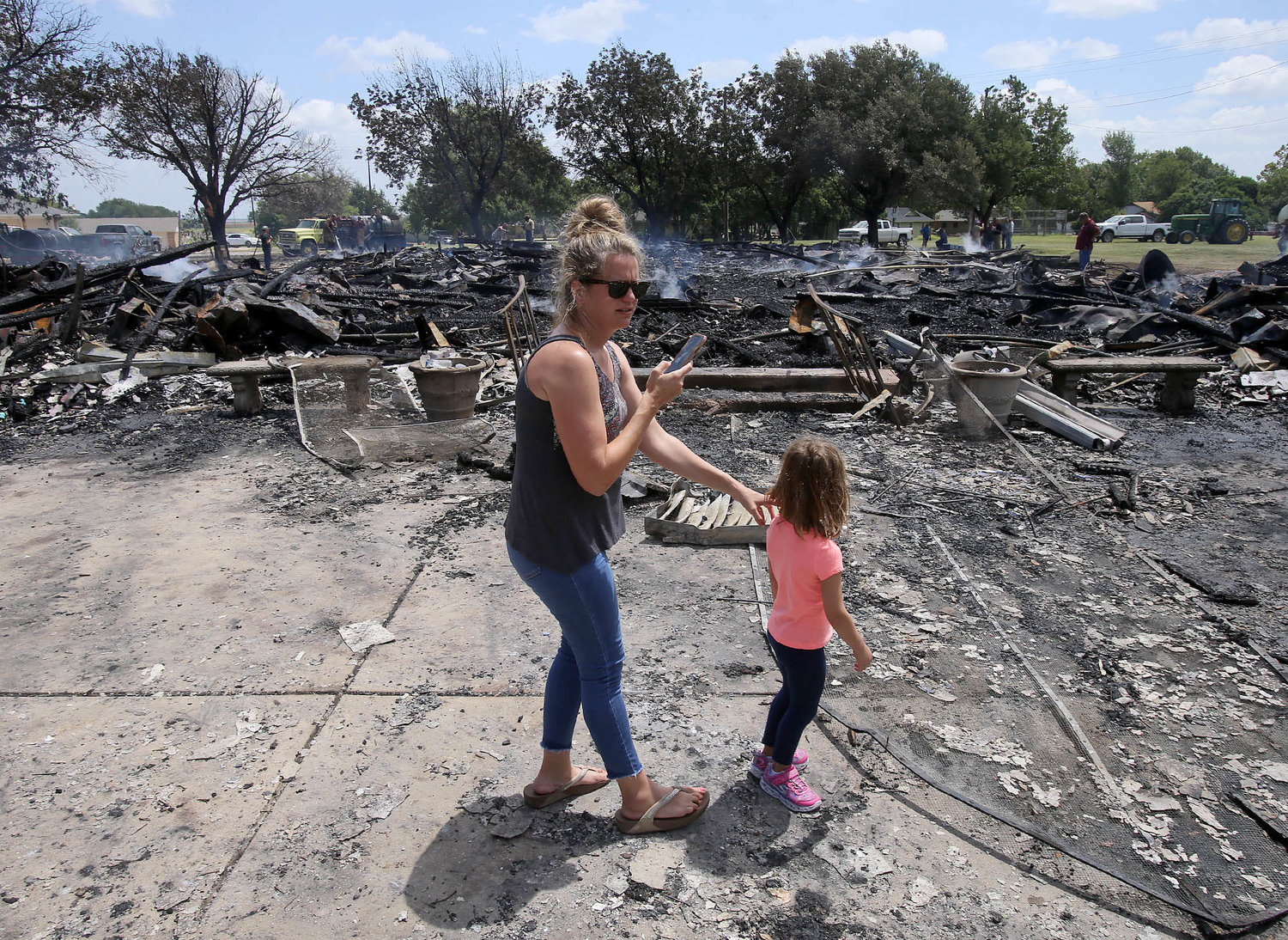Catherine Halfmann and her 4-year-old daughter, Emma, stand near debris July 29, 2019, after fire destroyed the Church of the Visitation in Westphalia, Texas. Since 1883 the parish has served the Catholic community of southwestern Falls County, many of whom are descendents of immigrants from the northwest German region of Westphalia.