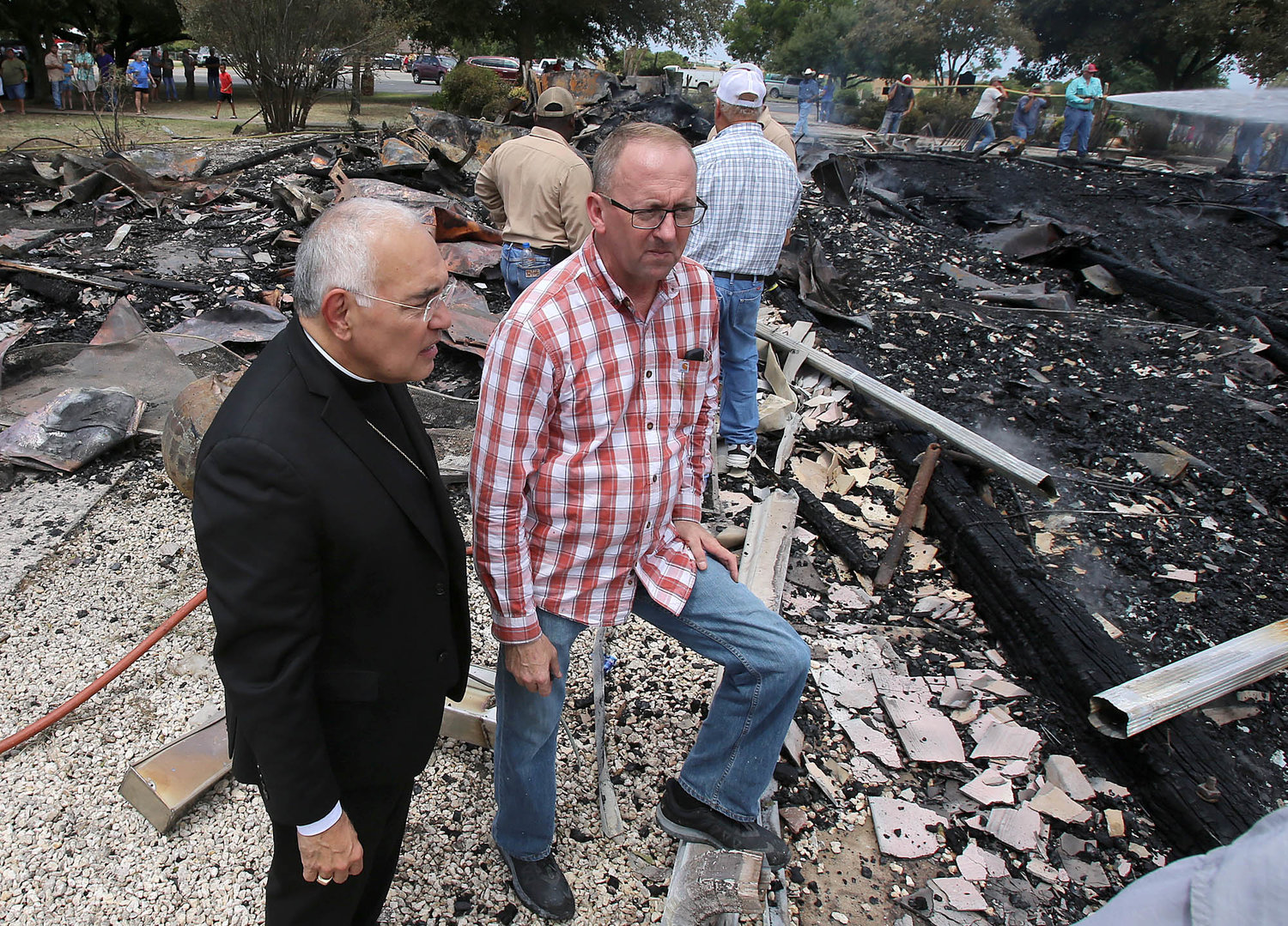 Bishop Joe S. Vasquez of Austin, Texas, and Father Darrell Kostiha, pastor at St. Joseph Parish in Cyclone and Sts. Cyril and Methodius Mission in Marak, look through debris of the Church of the Visitation in Westphalia July 29, 2019, after the 124-year-old church was destroyed in a fire. Since 1883 the parish has served the Catholic community of southwestern Falls County, many of whom are descendents of immigrants from the northwest German region of Westphalia.