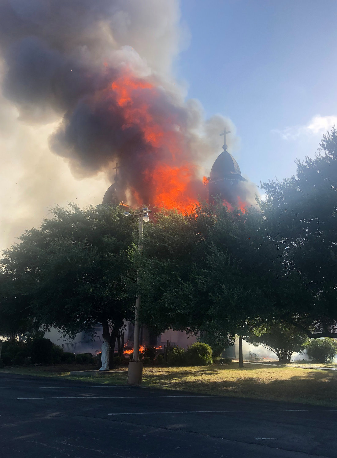 Flames and smoke billow out of the Church of the Visitation in Westphalia, Texas, July, 29, 2019. The nearly 125-year old wooden church with bell towers on each side, burned to the ground that morning. Since 1883 the parish has served the Catholic community of southwestern Falls County, many of whom are descendents of immigrants from the northwest German region of Westphalia.